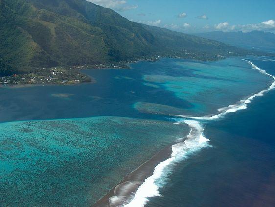 Survol de l'île de Tahiti par la côte ouest, avec le lagon, le récif et la haute-mer (l'océan). Au premier plan : la grande partie de Tahiti : Tahiti Nui. Dans l'arrière plan : la petite partie de l'île appelée Tahiti Iti. Et dans l'isthme : la ville de Taravao.