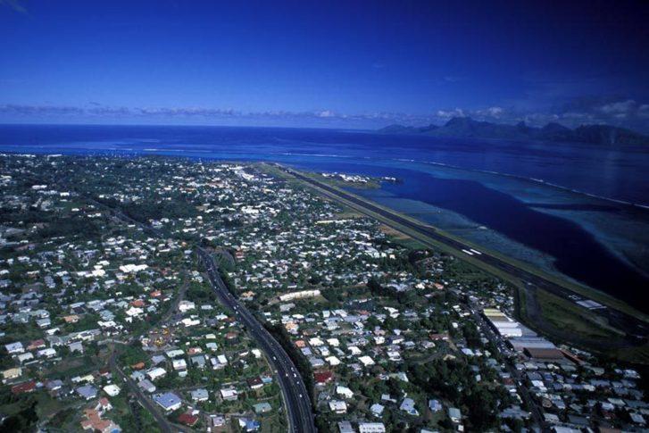 """Vue aérienne de l'aéroport international """"Tahiti - Faaa"""", de la commune de Faaa et vue sur l'île de Moorrea (c) Délégation de Polynésie Française à Paris."""