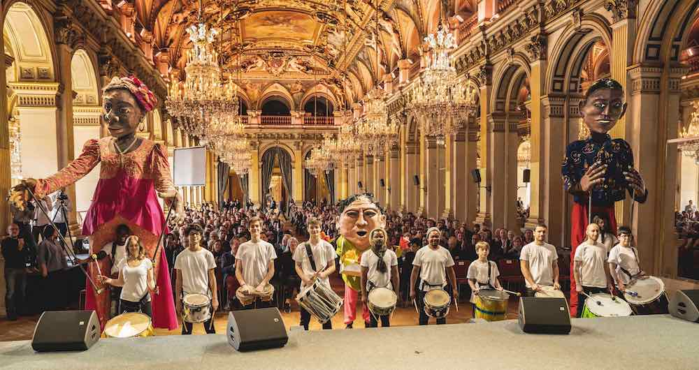 Giant Mozambique puppets, together with the band from Parade, at an earlier presentation in March 2019, all participants will march from Hôtel de Ville to the theatre on Friday next ©Thomas Amouroux, Théâtre du Châtelet