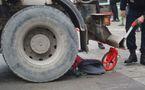 La poussette sous la roue arrière gauche du camion bétonnière.